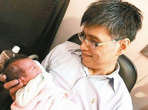 亚洲首对成功分割的坐骨连体双胞胎弟弟张忠义,妻子6月27日上午产下一对龙凤胎,他开心抱着孩子,迎接家中新成员。 图/张忠仁提供 来源 台湾《联合报》
