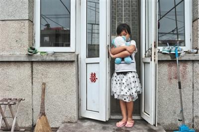 2016年6月29日,河北省秦皇岛市山海关区田庄村,一宁拿着本人最喜爱的小熊站在家门前,这座屋子是母亲果文婷和父亲刘博的婚房,门上的喜字是少数与刘博有关的物件。