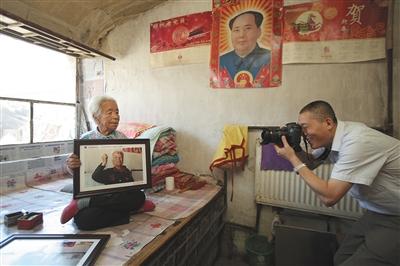 4月24日,延庆展出了450余张老党员相片,拍摄师亲身将王老太太的相片送到她的家中。新京报记者 彭子洋 摄