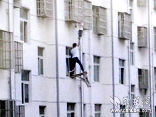 """杨林、陈华侨和物业工作人员等人按住板凳的一头,孙先生站在板凳的另一头""""托举""""孩子。"""