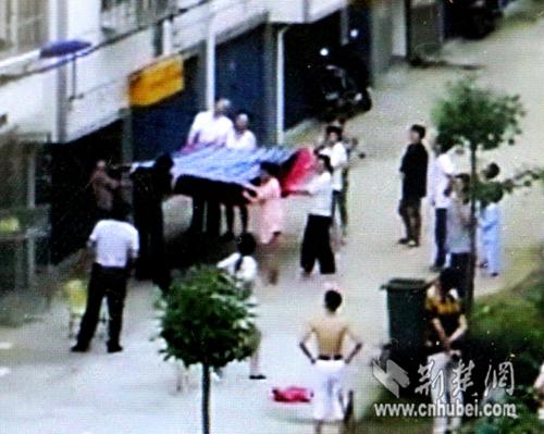 几名市民立即将棉絮和床单展开,等接在孩子的下方,防止其摔落下来。