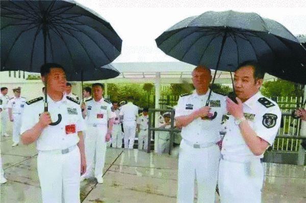 资料图:海军司令员吴胜利为电磁弹射专家马伟明打伞。