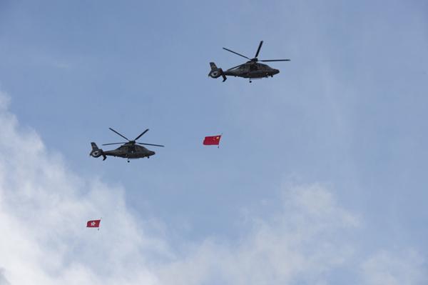 7月1日,吊挂国旗和香港特戋戋旗的直升机从金紫荆广场上空飞过。 新华社 图