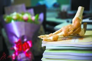 金大夫的工作桌上摆着踝骨模子,下面压着门生的论文;坐位上有共事怀想的鲜花。
