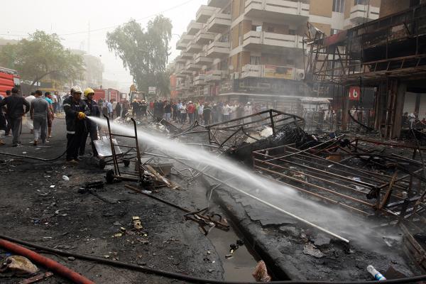 7月3日,在伊拉克首都巴格达卡拉达区,消防员在汽车炸弹袭击现场灭火。