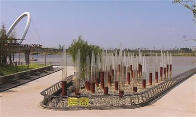 """建成时的""""长江影象""""雕塑,灯柱深色局部代表昔时最高水位,上半局部是LED灯。"""
