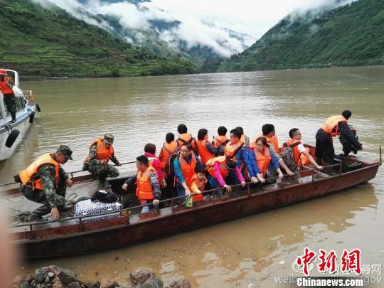 图为丽宁公路部分路段发生塌方,救援人员利用水上交通工具转移被困民众。 丽江市委宣传部官方微博 摄