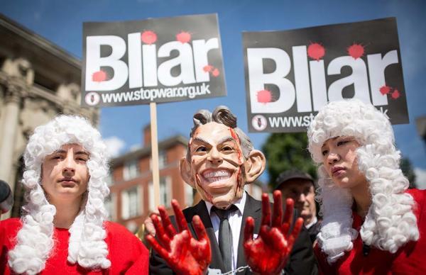 """本地时刻2016年7月6日,英国伦敦,大众头戴沾满""""血迹""""的前辅弼布莱尔和美国前总统布什的面具反对伊拉克和平。 东方IC 图"""