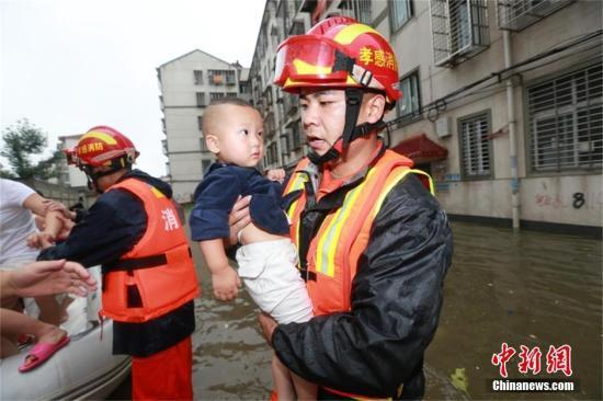 """7月6日,湖北省汉川市城隍镇一小区被淹,大量人员被困。由于积水已漫过楼道,橡皮艇无法靠近,为避免被困人员落水,消防官兵拱起大腿,架起""""桥梁"""",帮助被困人员转移。在浅水区,消防官兵抱起孩子,背起老人、妇女,将其转移到安全地带。经过3个多小时的营救,消防官兵往返多次,成功转移45名被困人员。王基达 摄 视频:湖北强降雨已致全省超1000万人受灾 来源:央视新闻"""