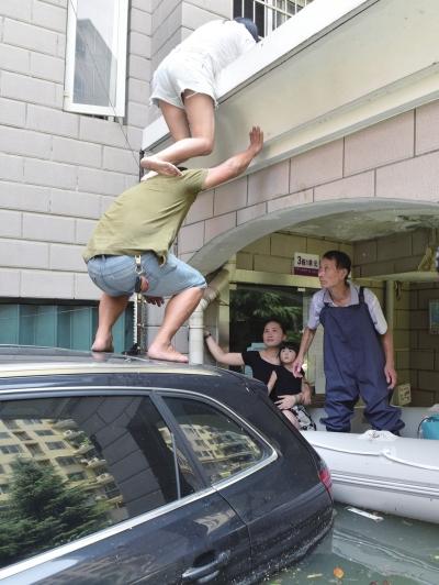 7月9日,由于楼道被淹,南湖一小区被困居民只能从二楼搭人梯转移。
