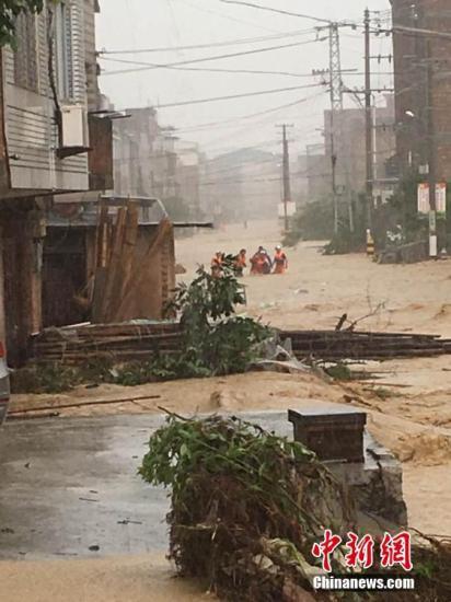 """7月9日13时45分,今年第1号台风""""尼伯特""""在福建石狮沿海登陆。受台风影响,强降雨侵袭福州,多地内涝严重。图为福州闽侯县受灾严重。 中新社记者 陈帆 摄"""