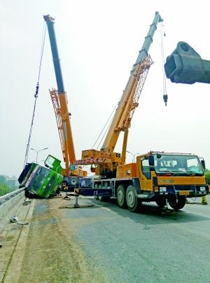 记者到现场时,两辆吊车正在将侧翻的货车拉起。