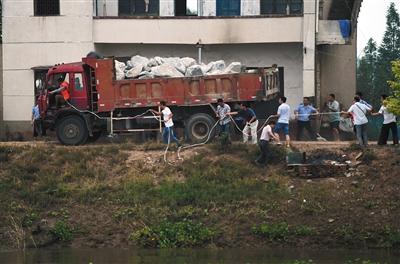 身系安全绳的抢险人员驾驶载满麻石的卡车驶向溃口。