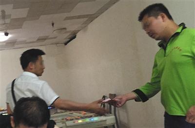 回龙观一电玩城暗室内,一男子(左)赌赢之后,工作人员将赌分换成现金交给他,男子称尽管赢回一些,当天仍输了3万多元。