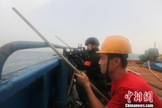 特战队员通过软梯登临舰载小艇。 谢坤 摄