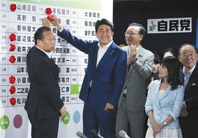 7月10日晚,日本东京,日本首相安倍晋三来到位于自民党总部的开票中心,为展板上写着的每个当选者的名字贴花。 图/视觉中国