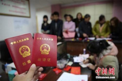 材料图:在某婚姻挂号处,新人在展现刚支付的成婚证书。 兰自涛 摄