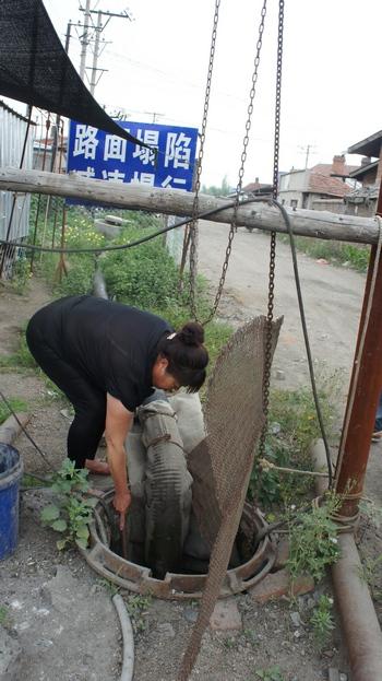 东京城镇:正在捞排水中垃圾的看泵人