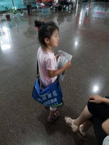 宁安市文教幼儿园中二班姚佳翼正在宁安市火车站向旅客卖报