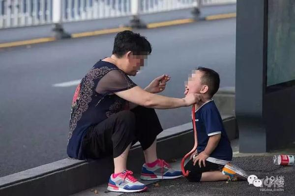 杭州一大妈坐马路边 边抽烟边让孙子学狗爬用嘴叼蛇