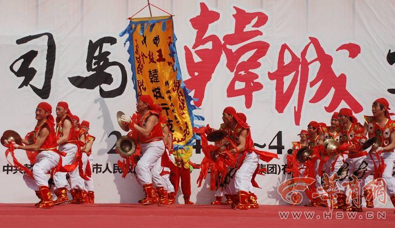 """韩城行鼓俗称""""挎鼓子"""",激昂的鼓点敲响,身着鲜艳的服饰的黄河汉子以骑马蹲裆之势摆开阵势,令旗挥舞,锣鼓齐鸣,击声如雷,吼声震天,尽显黄河汉子的热情、粗犷、豪爽、彪悍之英气。"""