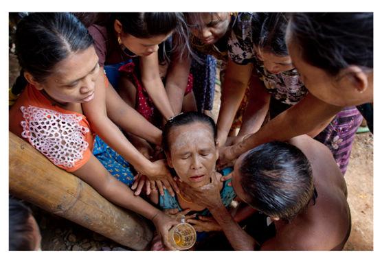 一众妇女围绕着钦比。这个女人刚刚和她的儿子团聚,随后便因为体力透支晕倒了过去。感谢美联社的获奖系列报道《血汗海鲜》,钦比是数百名返回到缅甸的、被奴役过的渔民之一。