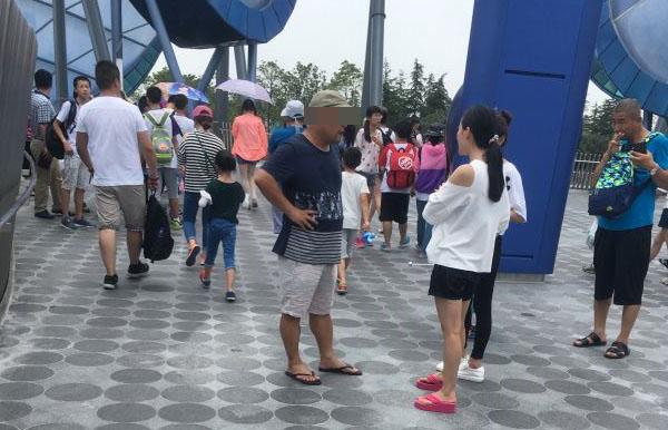 """在""""创极速光轮""""入口处,一名黄牛(前排左一)与游客谈价钱,自称可直接带人进去,不用排队。"""