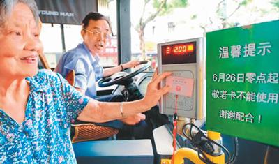 """上海老人使用老年卡刷卡上车,旁边""""六月二十六日零时起,敬老卡不能使用""""的提示吸引了她的注意。"""