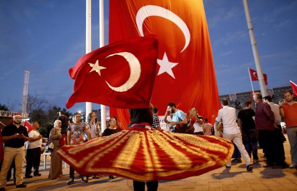本地时刻2016年7月18日,土耳其伊斯坦布尔,一位女子在庆贺流动上举着国旗扮演扭转舞。 东方IC 图