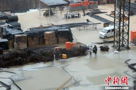 20日上午,保定市区一建筑工地被雨水淹没,工人冒雨安放水泵排水。 于俊亮 摄