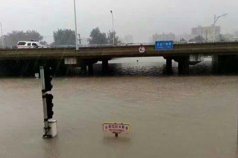 """新京报快讯(记者左燕燕)今天下午,由于持续暴雨,大红门东桥北侧积水将北侧辅路200米左右路段淹没,只能看到""""南四环中路""""路标的顶部和红绿灯的顶端,一处涌水点正在不断冒水。"""