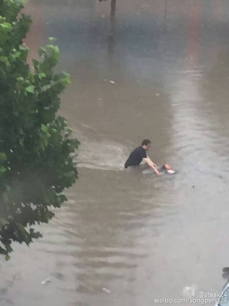 图为一名戴眼镜的男子赶到附近,将差点被积水淹没的女子扶了起来。