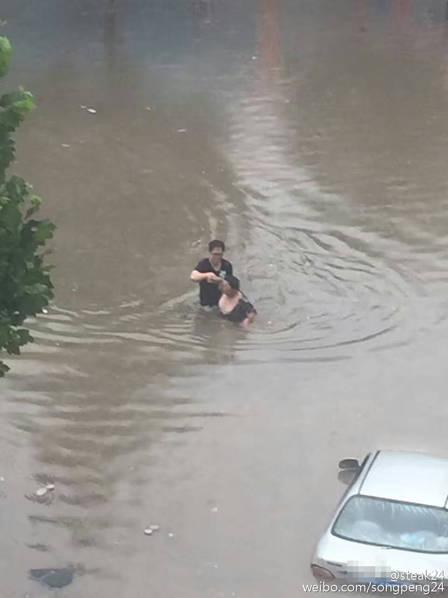 男子扶着女子慢慢走出积水位置。