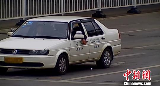 图为被拍下的车窗抛物不文化举动 城管部分供给 摄