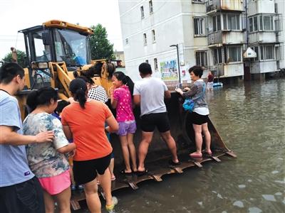 昨日,大兴隆盛园小区,进出小区的道路被淹没,居民乘铲车回家。新京报记者 王煜 摄