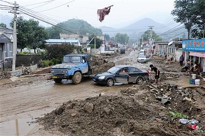 """2012年7月25日,房山区北车营村,""""7・21""""暴雨后,被洪水冲过的街道一片狼藉。"""