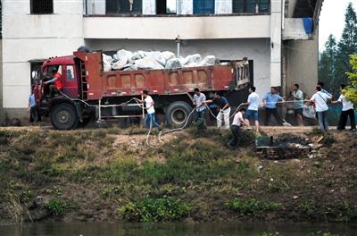 7月10日,湖南省华容县新华垸出现溃口。身系安全绳的抢险人员(左一)驾驶着载满麻石的卡车驶向溃口。新华社发