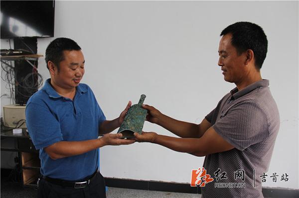 张智林将战国�纹乳钉青铜扁钟上交给吉首市文物局。