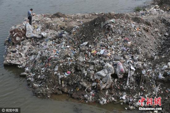 资料图:2016年7月17日,江苏省海门市的江心沙农场新江海河一座桥附近偷倒的垃圾。据运载垃圾货船上的船员透露,这些垃圾也是从上海运来。视觉中国