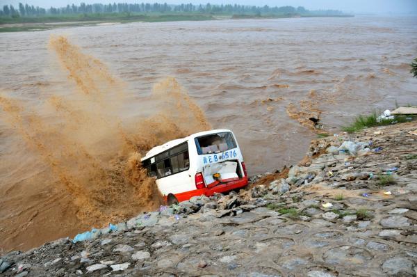 2016年7月21日,河北省沙河市,抢险人员在大沙河高庙段用装有沙袋的报废公交车抢筑堤坝。 视觉中国 图