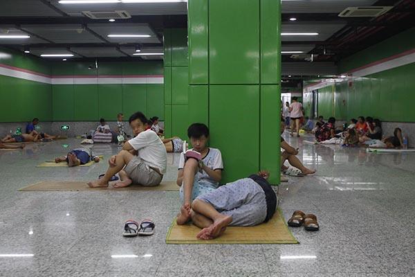 2016年7月24日,上海地铁金沙江西路站,由于天气太过炎热,一些家中尚未配备空调的打工者选择拖家带口到地铁站内避暑。 澎湃新闻记者 韦毅 图