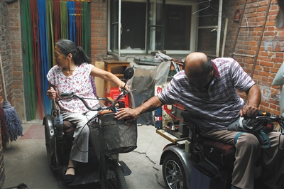 7月16日,杨玉芳帮高志宏调整电动轮椅车。