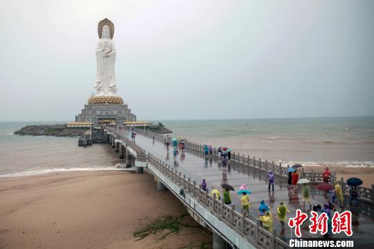图为27日,游客在三亚南山景区游玩。 吕志强 摄