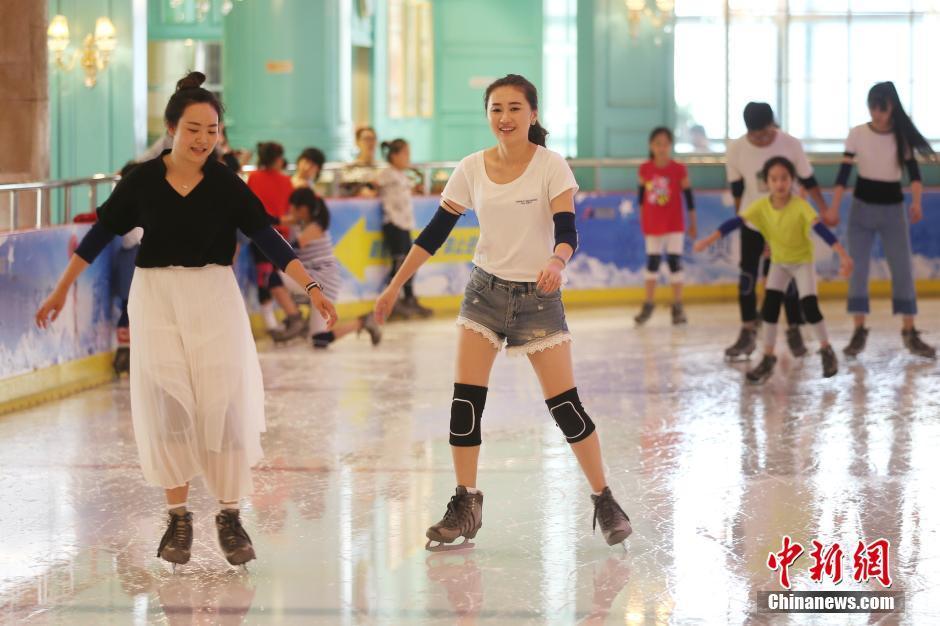 """7月27日,市民在南京一家滑冰场内滑冰。近日的江苏南京持续""""高烧"""",炎热的天气使当地民众减少了户外出行,纷纷前往室内滑冰场、商场、图书馆等场所避暑纳凉。 中新社记者 泱波 摄"""