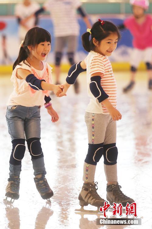 """7月27日,小朋友在南京一家滑冰场内滑冰。近日的江苏南京持续""""高烧"""",炎热的天气使当地民众减少了户外出行,纷纷前往室内滑冰场、商场、图书馆等场所避暑纳凉。 中新社记者 泱波 摄"""