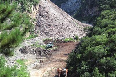 今天,挖土机正在清算渣滓山。京华时报记者陶冉摄