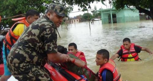 """尼泊尔军方发布的照片显示,一些村民爬到屋顶上等待救援。达卡尔说:""""我们正处于高戒备状态,我们的搜救队伍还在漏夜进行搜救行动。"""""""