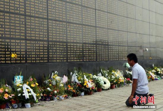 图为市民在罹难者纪念墙前下跪缅怀。 韩冰 摄