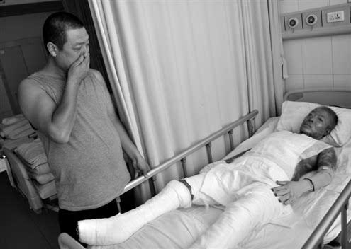 孙百群看着躺在病床上身上裹满纱布的妻子潸然泪下