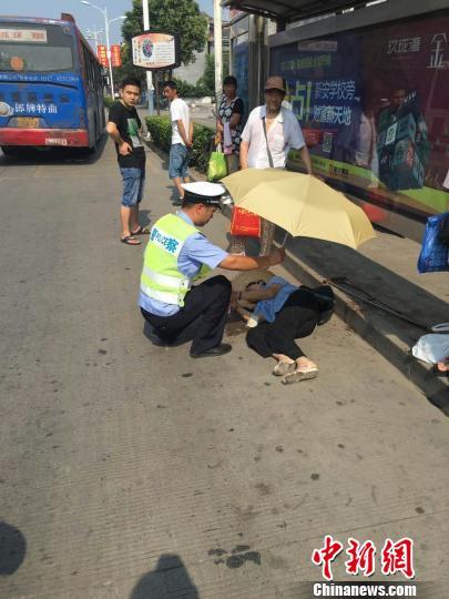 交警在烈日下为中暑晕倒的老人撑起遮阳伞。目击者供图 郭亚楠 摄